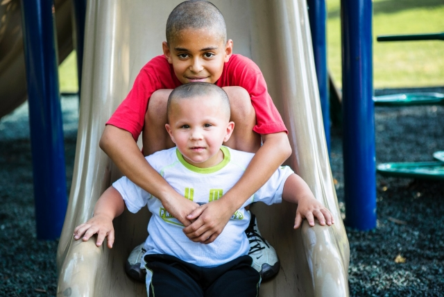 Two boys play on a slide on a playground in North Carolina.