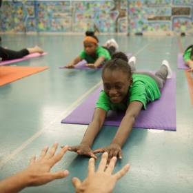 A child stretches out on a yoga mat.