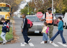 Children walking to school; a Crossing Guard helps them cross the road.