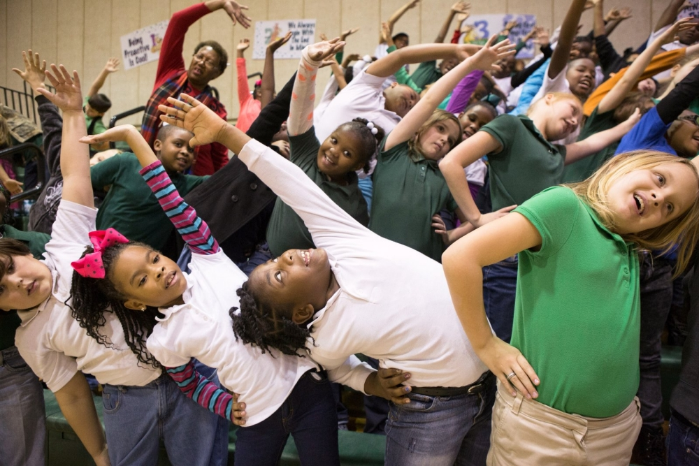 Students stretch and play in a classroom with their teacher.