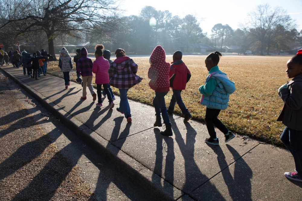 Students walk to school on a sidewalk next to a park.