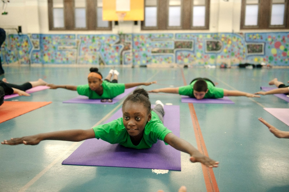 Students doing yoga in gymnasium.