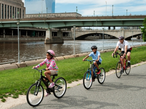 A family rides bicycles together along a river.