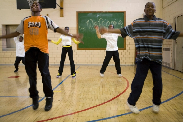 Students do jumping jacks in a school gym class.