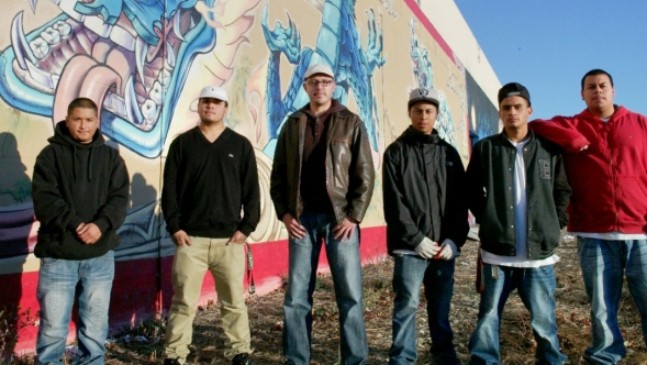 A Latino men's group poses in front of artwork painted on a building.
