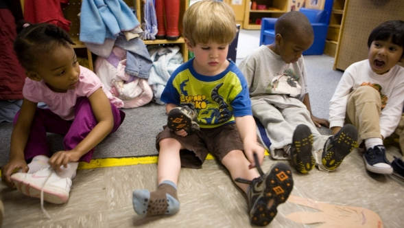 Two young children putting on or taking off their shoes