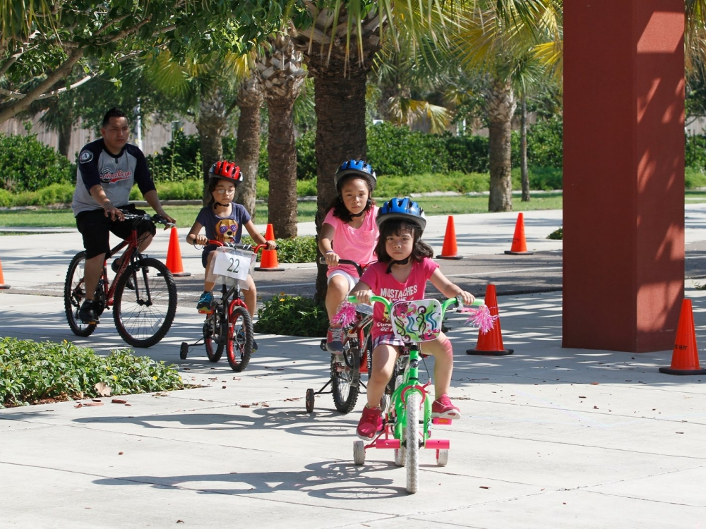 Children ride bikes through the park.