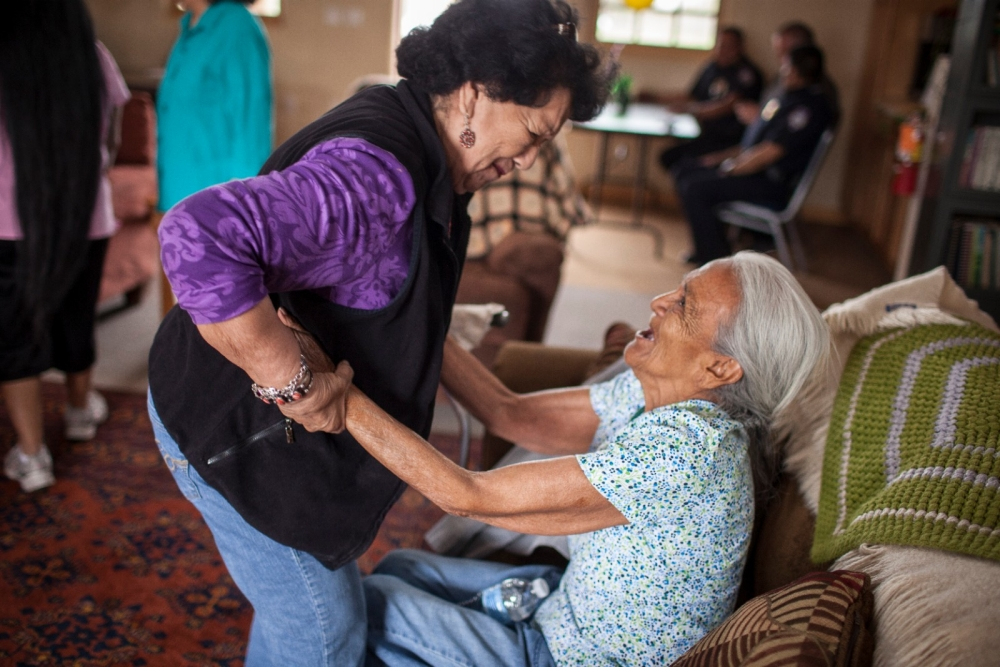 A nurse helps an elderly woman stand up.