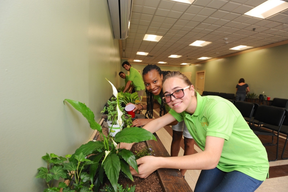 Students from Berea College plant flowers in the Williamson Health and Wellness center.