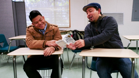 Two men sit at desks in a classroom and discuss a book.
