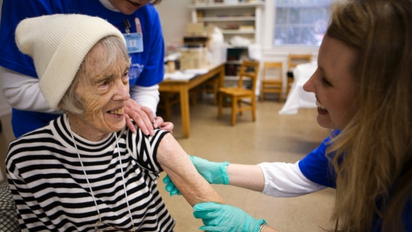 An elderly woman receives a flu vaccination.