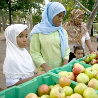 A woman and her children shop at a farmers' market.