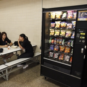 Student buys snack from vending machine.