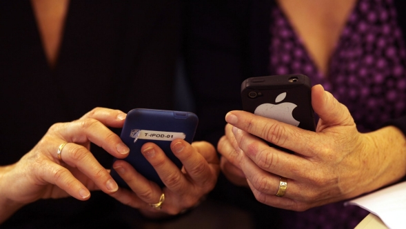 Two women comparing mobile phones.