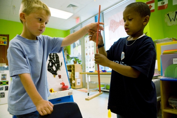 Two boys work together on a kindergarten building project.