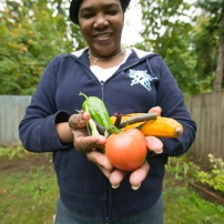A woman holds some vegetables she has grown in her garden.