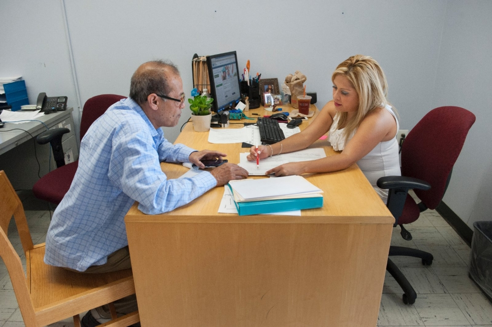 A counselor meets with a client about health services.