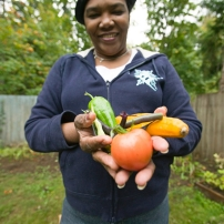Woman shows off vegetables from her garden