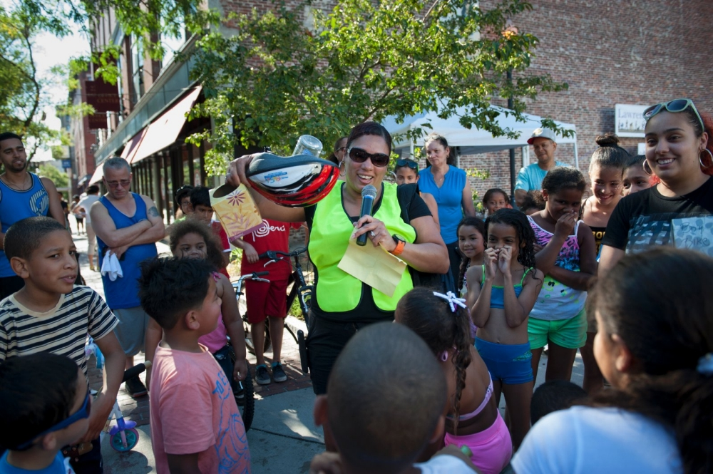 Community leader Vilma Lora conducts the Ciclovia raffle, in which the town gifted people with helmets and bikes.