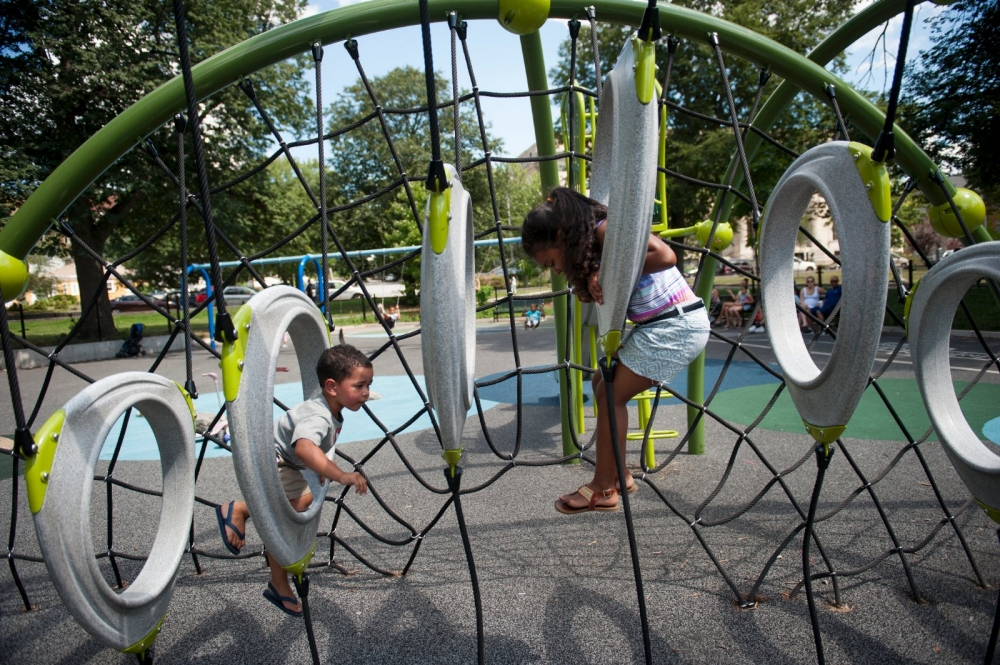 Children climb on the jungle gym in the new playground in Lawrence's Campagnone Common.