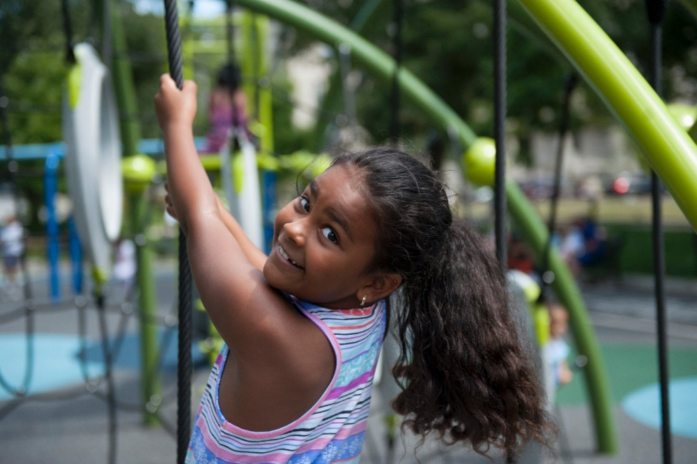 A girl climbs on the jungle gym in the new playground in Lawrence's Campagnone Common.