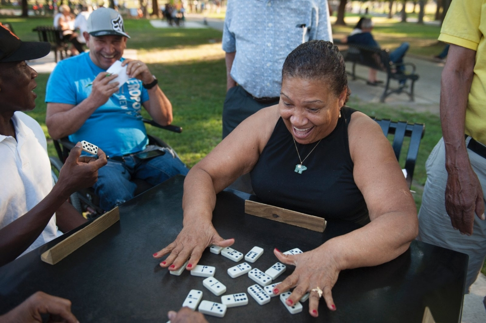 A woman plays dominos with friends on the new tables at Campagnone Common in Lawrence.