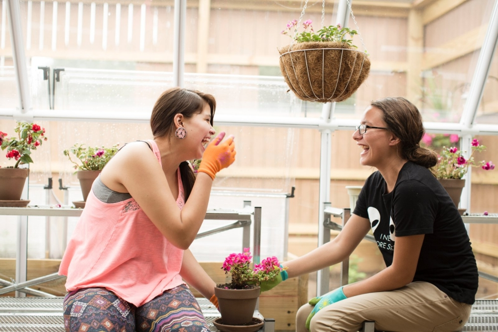 Two Menominee Indian Middle School students laugh as they work in the school greenhouse.