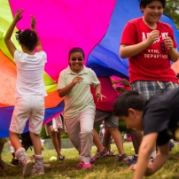 Children play with a colorful parachute in Durham, N.C.