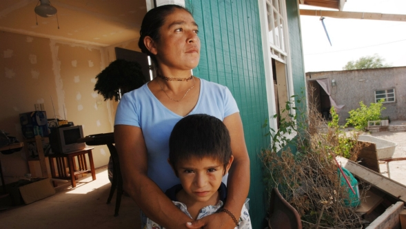 A woman stands outside a house with her arms around her son.