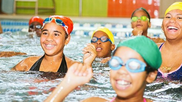 A group of swimmers gather at a communitiy pool.