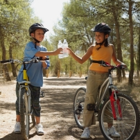 A boy and a girl on bikes, holding water bottles.