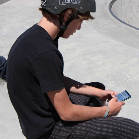 A boy sitting on a wall, wearing a skateboard helmet and using a hand held device.