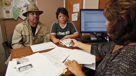 A medical professional helps patients fill out forms for medical insurance.