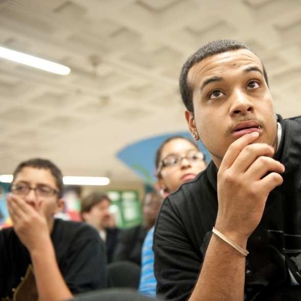 Young men listen to a speaker at a meeting.