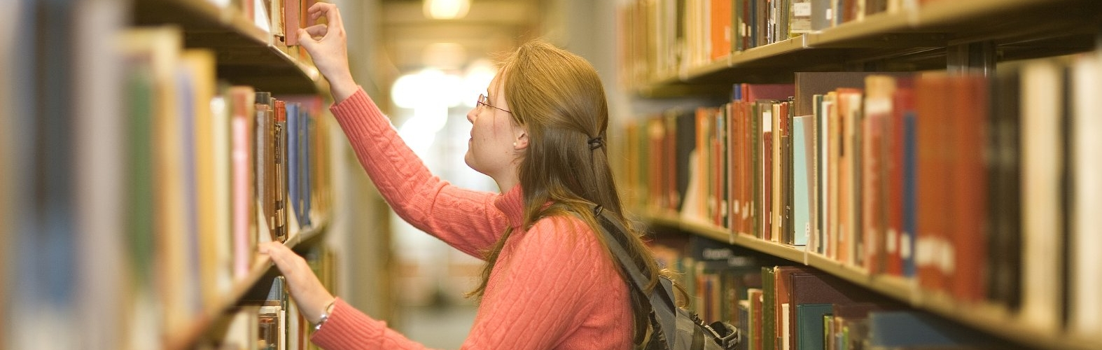 Young woman does research in a university library.