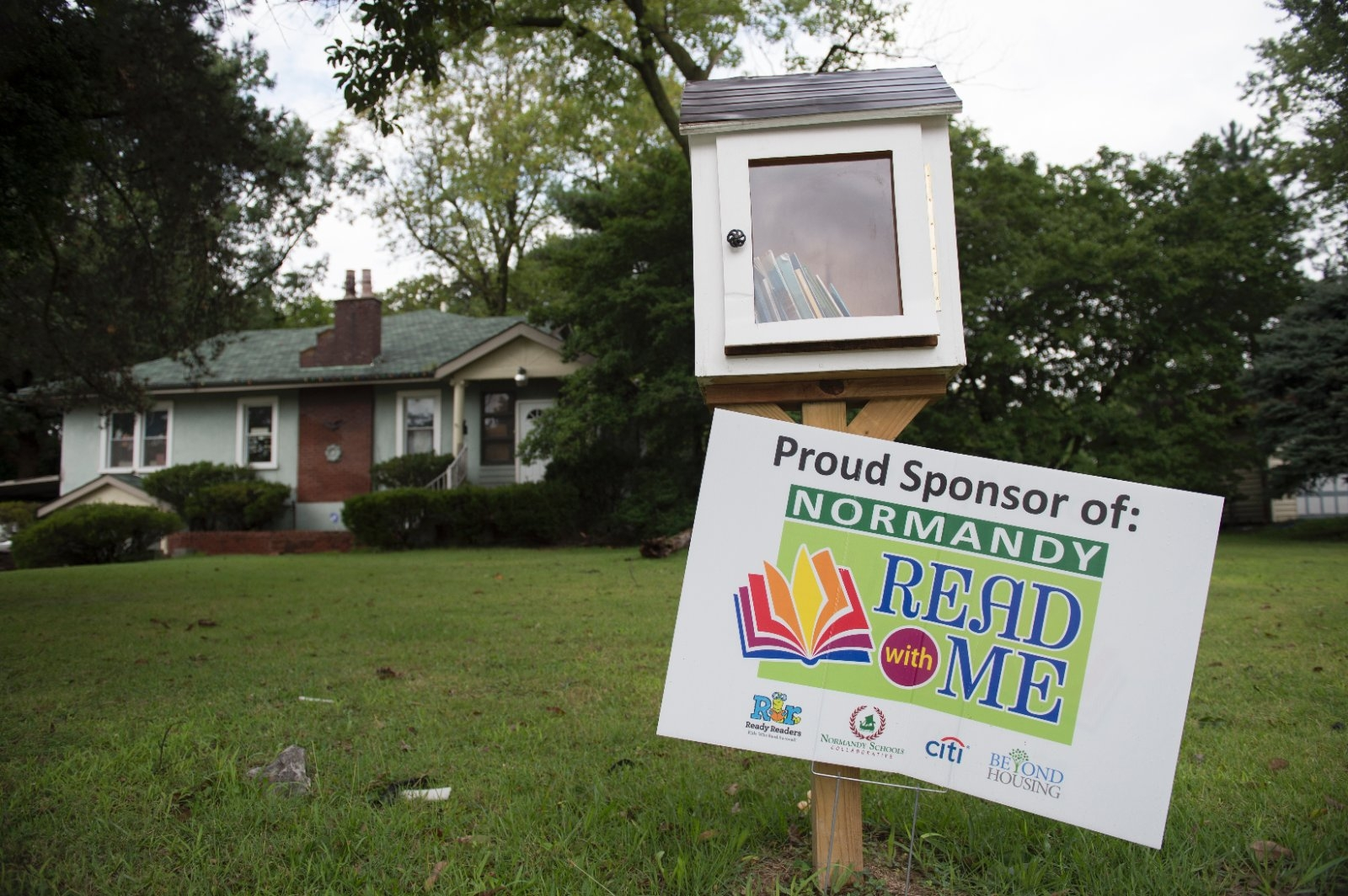 Lawn sign promoting community reading program.