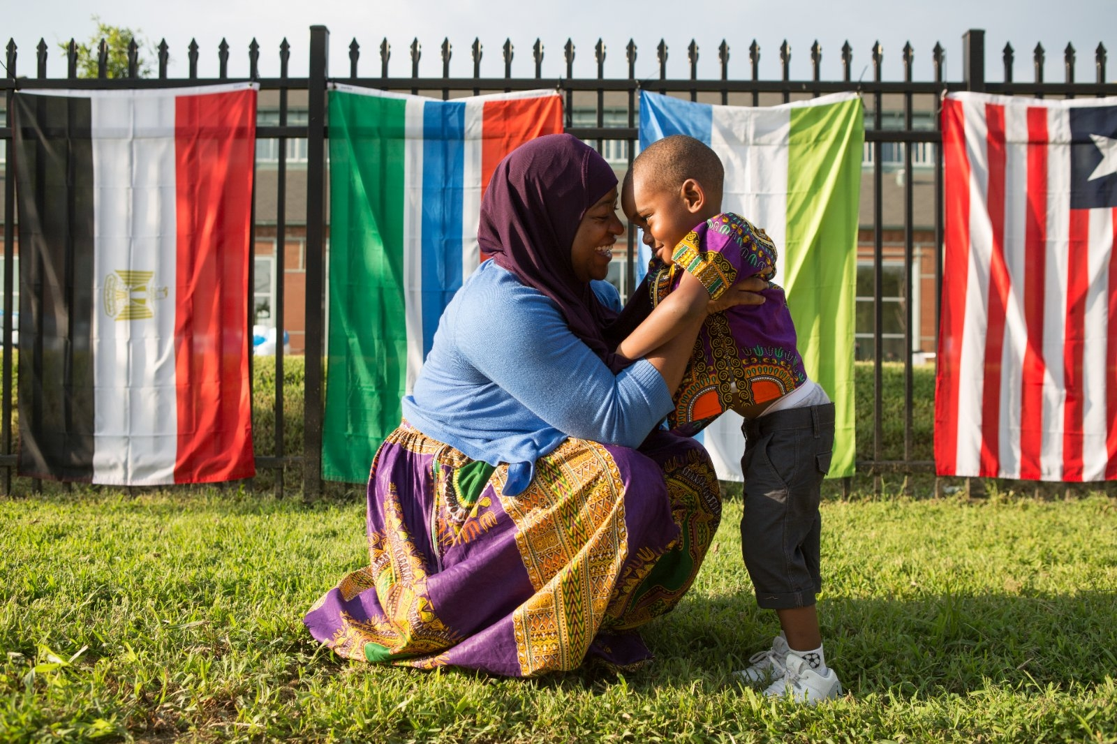 A woman smiles at her son in front of the African nations' flags.