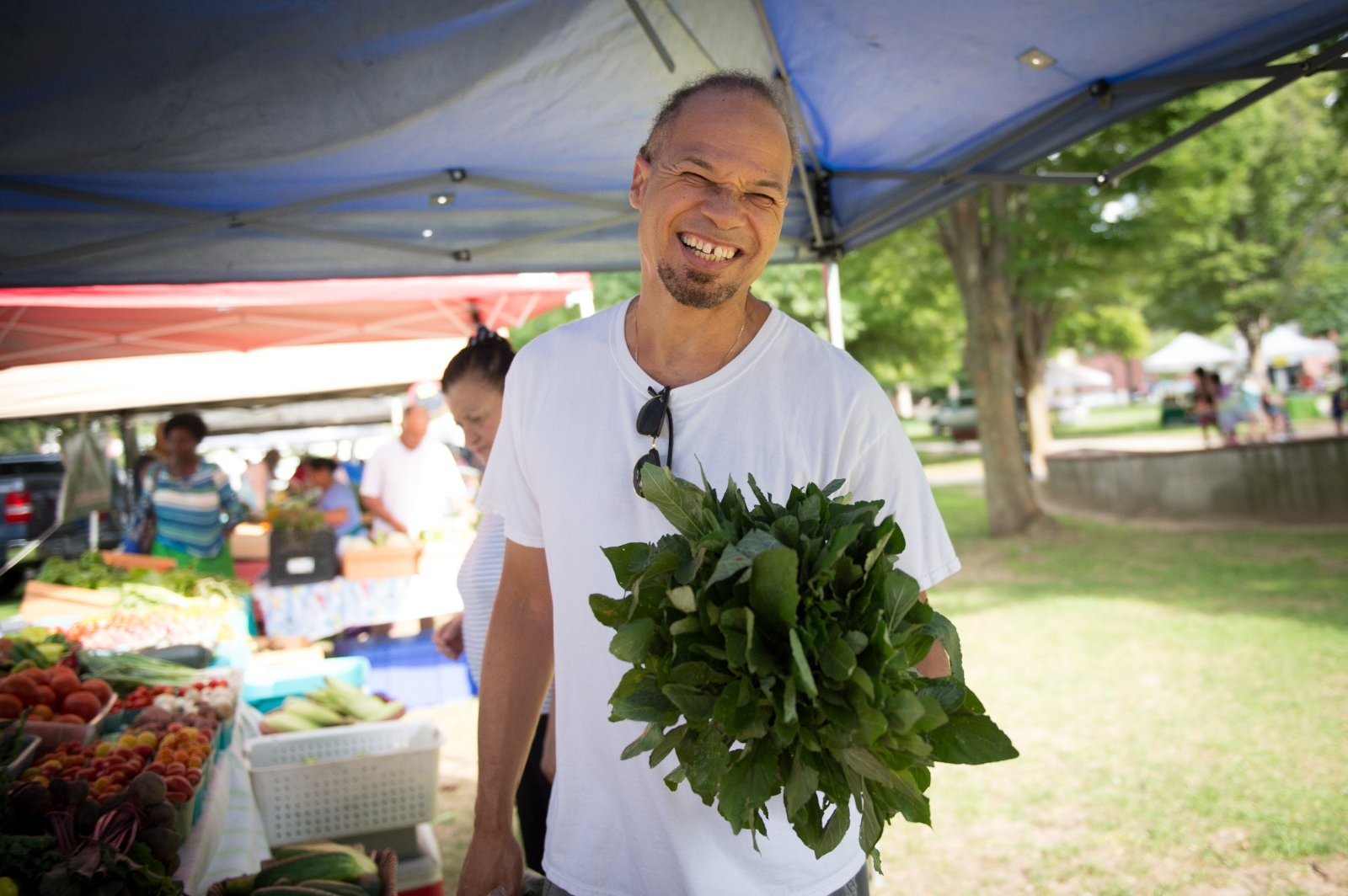 A man shops for greens at a farmers' market.