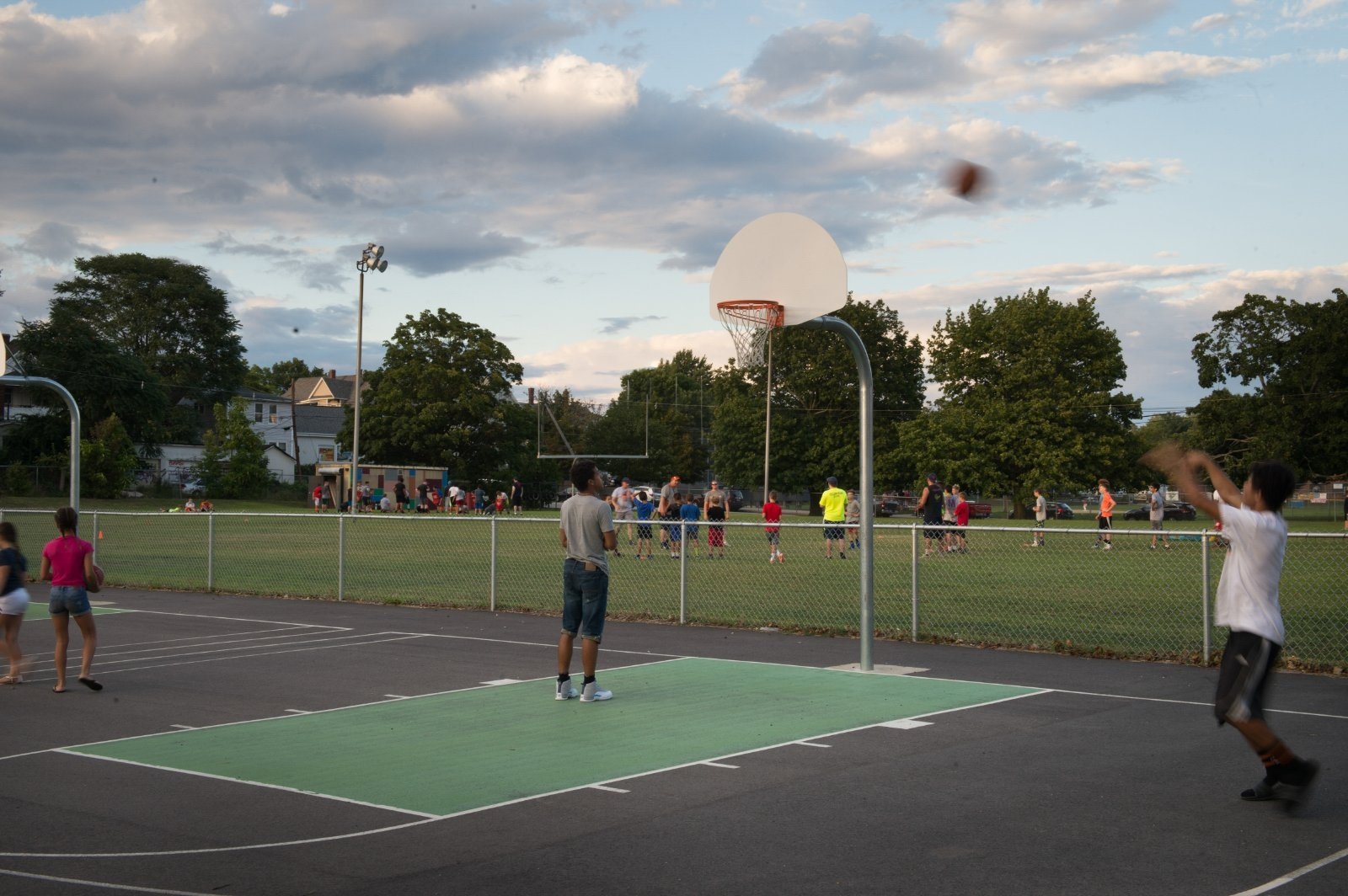 Young men play on a new basketball court.