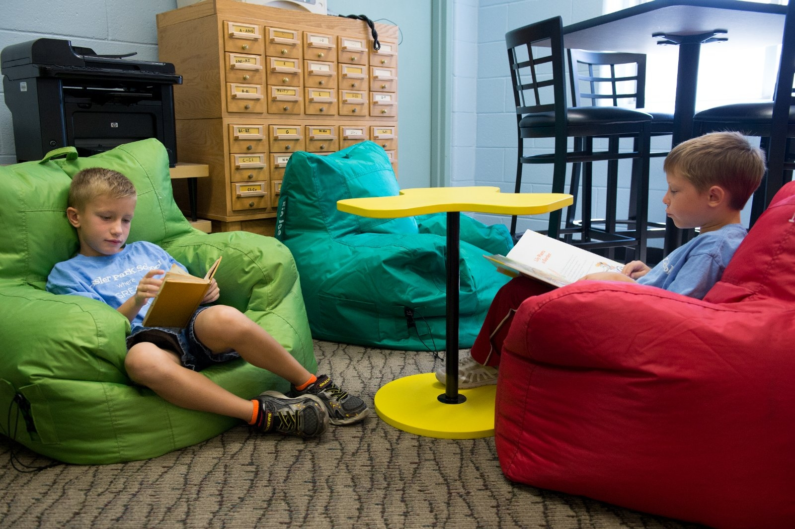 Students sit in bean bag chairs and read.