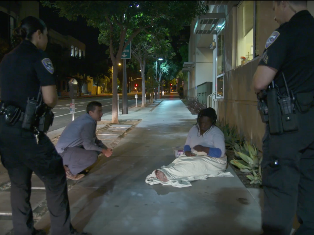 Police officers speak with a homeless woman.