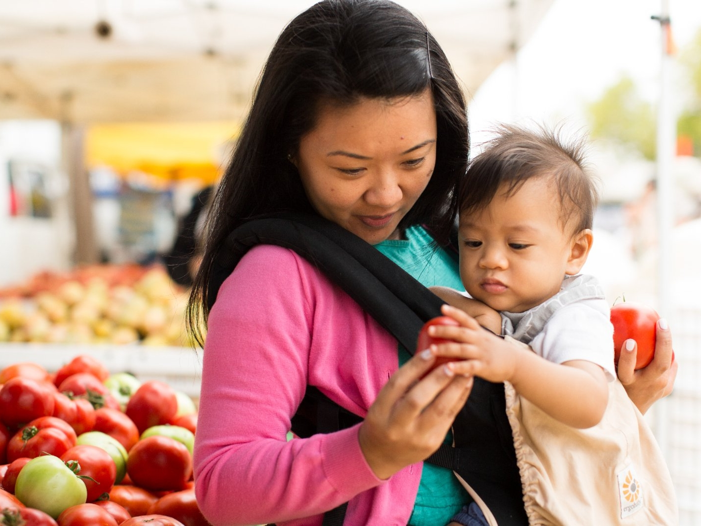 A woman and her baby at a farmers' market.