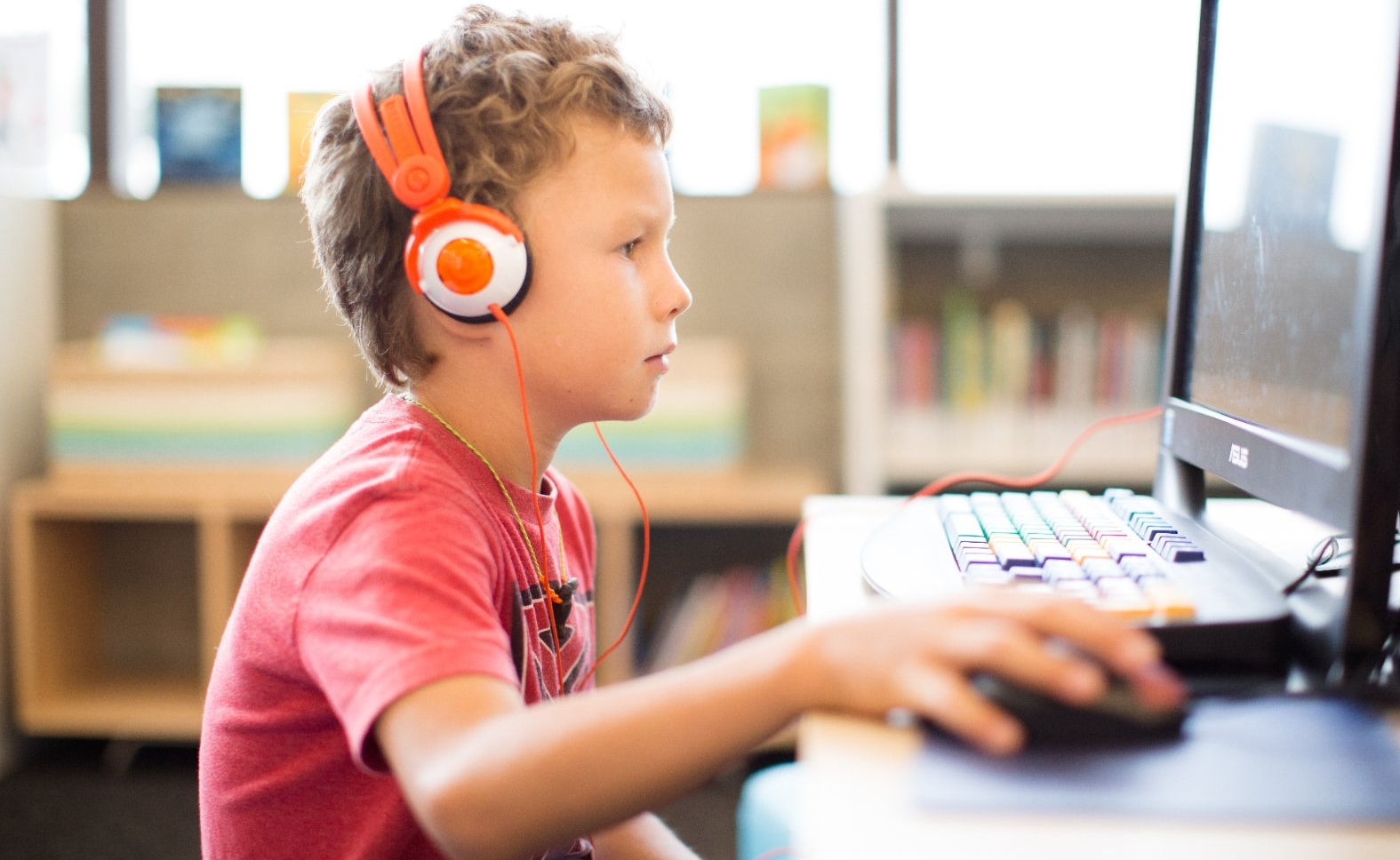 Boy uses headphones and computer at the library.