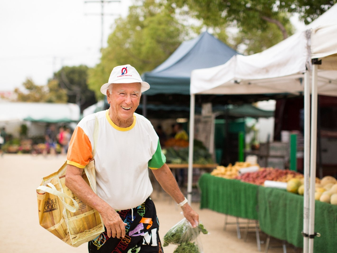 A man carries produce after shopping at farmers' market.