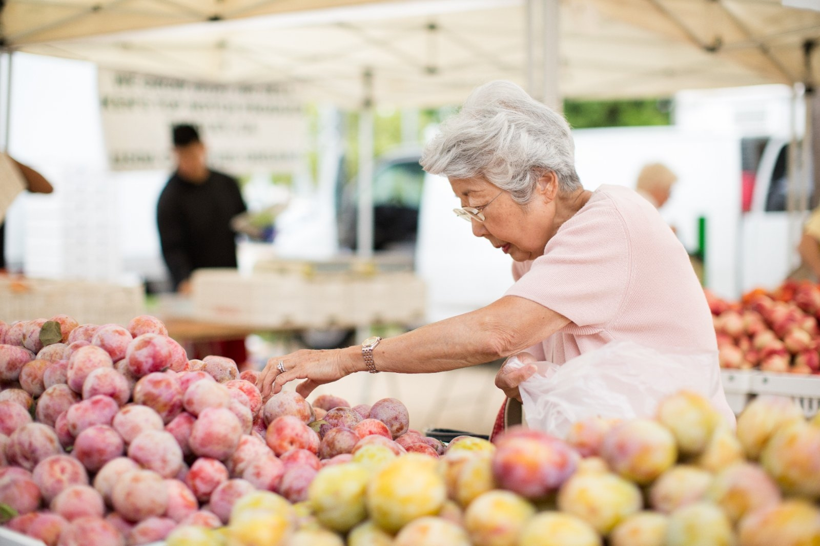 A woman browses fresh fruit at a farmers' market.