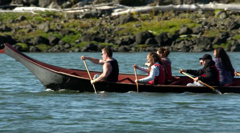 People paddle in a hand carved boat.