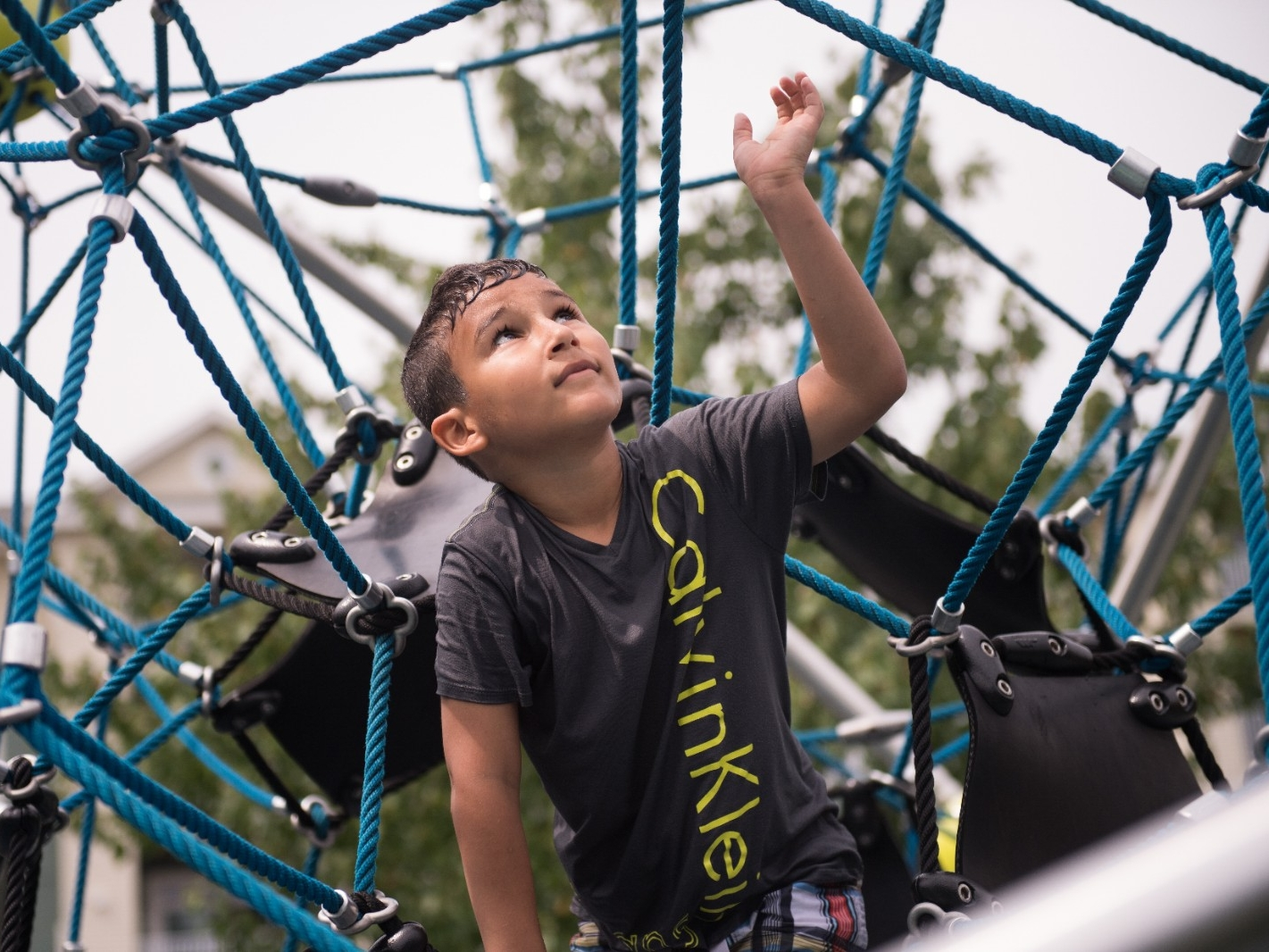 A boy plays on a jungle gym.
