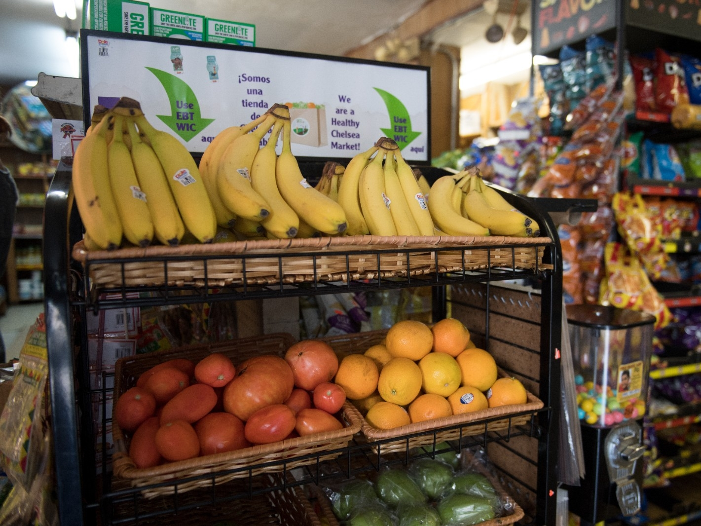 A fruit and vegetable display inside a corner store.