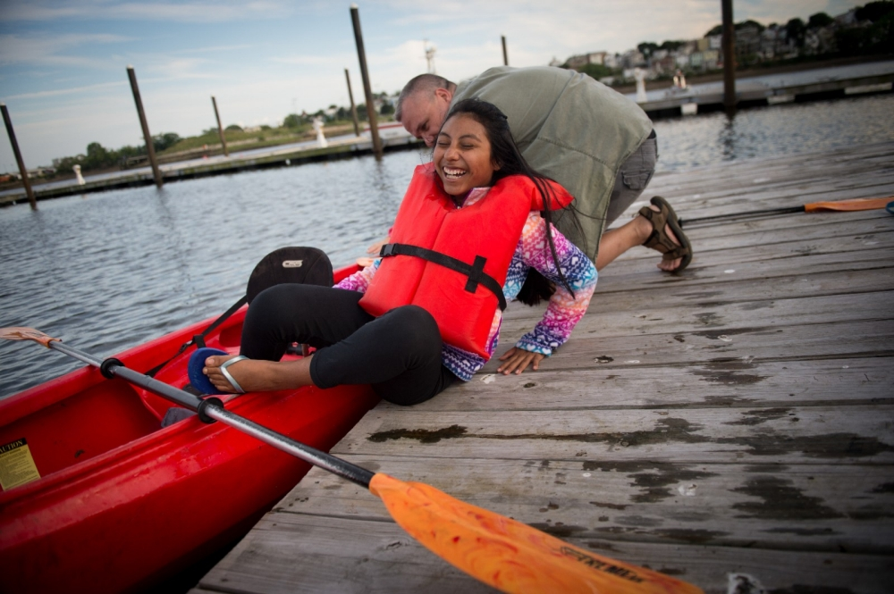 A girl gets out of her kayak during a kayaking event.