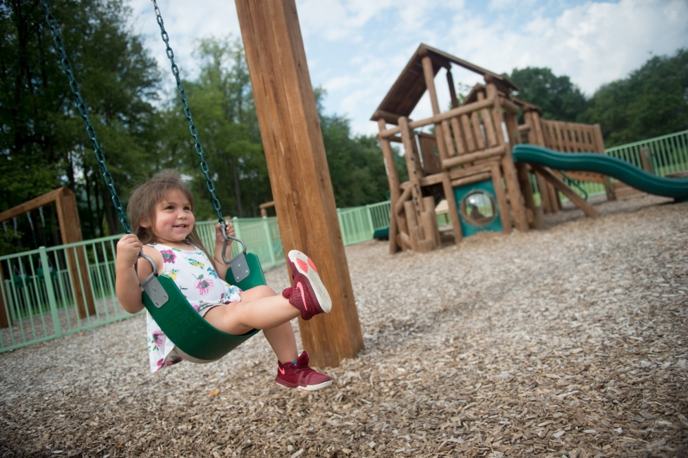A little girl swings on a playground.